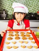 la bambina asiatica offre il biscotto delizioso in cucina foto