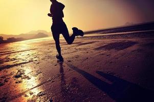 giovane donna fitness in esecuzione sulla spiaggia di alba foto