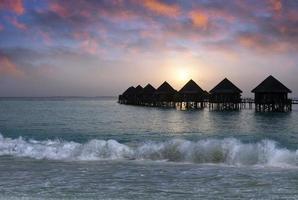 pile di villa sull'acqua al momento del tramonto. Maldive.