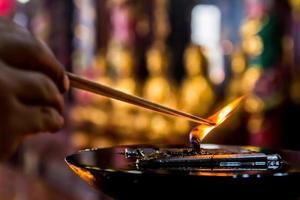 grande lampada a olio con mano prende un bastoncino d'incenso sparato
