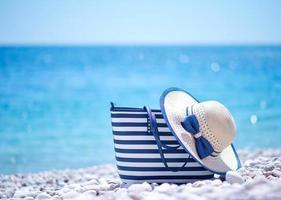 borsa e cappello sulla spiaggia foto