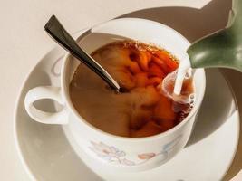 il latte viene versato nella tazza di tè sul tavolo foto