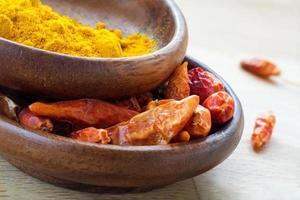 spezie asiatiche, peperoncino rosso essiccato e curcuma in ciotole di legno foto