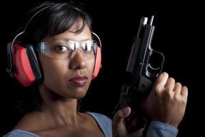 donna che indossa protezioni per gli occhi e le orecchie a portata di pistola foto