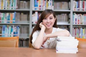 la bella studentessa asiatica ha letto il libro in biblioteca foto