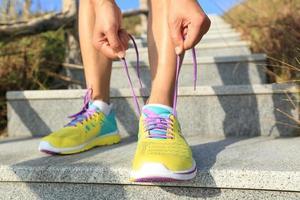 corridore di giovane donna che lega i lacci delle scarpe sulla pista di pietra foto