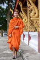 giovane monaco buddista che cammina accanto al tempio foto