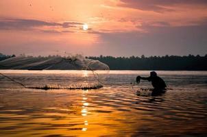 pescatore che lancia una rete da pesca foto