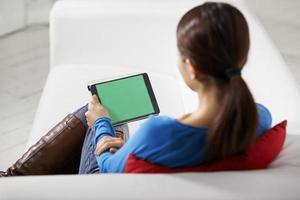 ragazza asiatica che per mezzo del dispositivo del touchpad foto