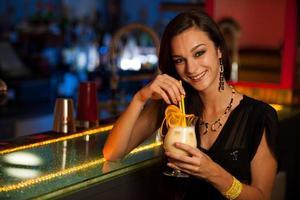 ragazza beve un cocktail in discoteca foto