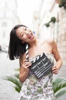 giovane donna asiatica sorridente mostra bordo batacchio