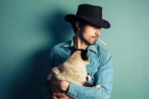 il giovane cowboy con il gatto sta fumando foto
