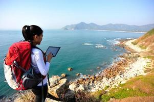 escursionismo donna uso tablet pc mare foto