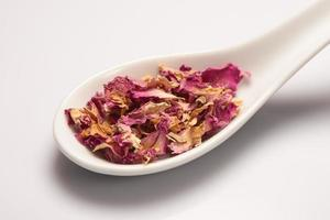 mucchio di foglie secche di rosa in un cucchiaio di ceramica bianca foto