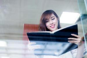 bello libro asiatico della tenuta della studentessa in ritratto delle biblioteche foto