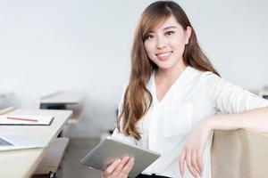bello studio asiatico della studentessa con la compressa in aula foto