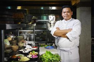 cuoco unico asiatico che sorride alla macchina fotografica nella cucina del ristorante