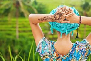 donna con mehendi tatto sulla sua mano nel campo di riso foto