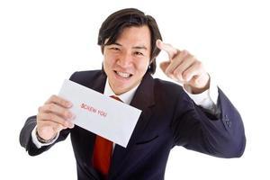uomo d'affari asiatico arrabbiato che punta alla fotocamera, busta dice fottiti foto