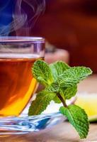 tè in una tazza di vetro, foglie di menta foto