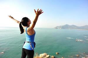 escursionismo donna alzò le braccia al mare blu foto