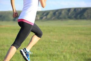atleta del corridore che funziona sul campo di erba pieno di sole foto