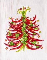 albero di Natale caldo del peperoncino rosso su fondo di legno bianco, vista superiore foto