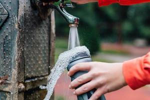 primo piano della donna che versa acqua in una bottiglia di sport