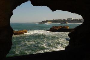 faro di Biarritz attraverso il foro nella roccia foto