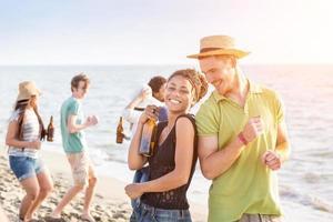 gruppo multirazziale di amici che hanno una festa in spiaggia foto