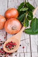 cipolle fresche, foglie di alloro e grani di pepe in un cucchiaio foto