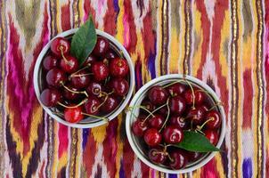 ciotole con ciliegia matura sopra la tradizionale tovaglia orientale