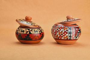 due vasi in ceramica dipinti a mano con coperchi su carta kraft foto