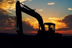 sagoma dell'escavatore nella luce del tramonto. foto