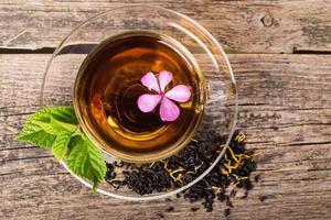tè con fiore rosa e foglia di menta, su legno
