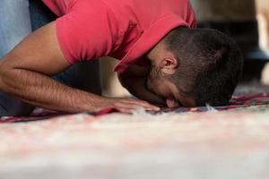 giovane ragazzo musulmano che prega foto