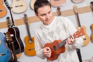 uomo che suona ukelele nel negozio di musica foto