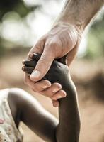 mano del bambino africano che tiene una mano bianca per adulti foto