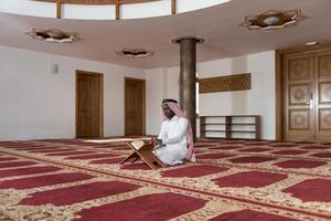 uomo d'affari nero in Dishdasha sta leggendo il Corano