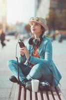 ragazza dei pantaloni a vita bassa nella musica d'ascolto di cappello e occhiali
