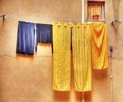 vestiti gialli e blu appesi su un filo stendibiancheria foto