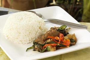 coscia piccante di maiale in padella e riso bianco al vapore foto