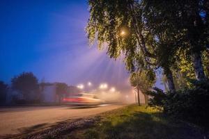 strada di città di notte con nebbia. luci e automobili foto