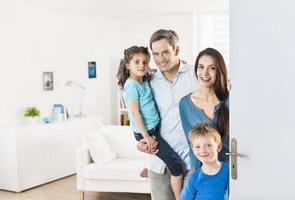 famiglia in piedi davanti alla porta per invitare le persone a casa foto