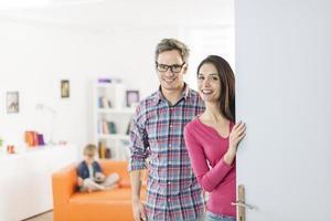 coppia invitando le persone a entrare in casa alla porta foto