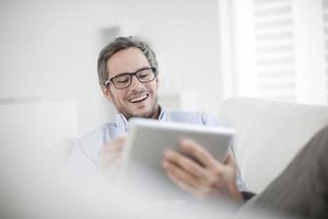 uomo attraente a casa utilizzando la tabella digitale foto