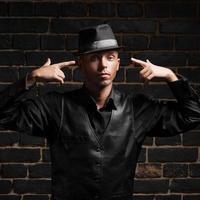 uomo alla moda contro il muro di mattoni nero foto