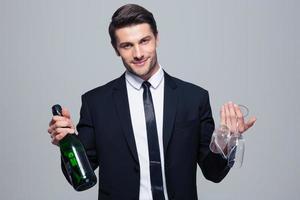 bottiglia della holding dell'uomo d'affari con champagne e vetro foto