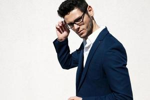 giovane uomo bello che indossa gli occhiali di moda su sfondo neutro con foto