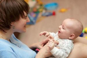 la madre solletica il suo bambino foto